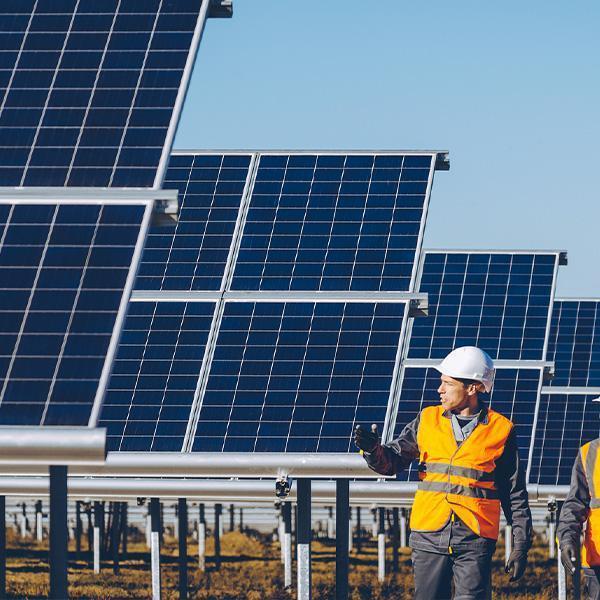 Mężczyzna wkamizelce odblaskowej ikasku natle paneli słonecznych